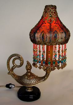 Enchanting little vintage genie lamp from Europe is topped with a Sheik shaped shade. Shade is covered in beautifully colored net lace from France and exquisite gold metallic trim at the top. Jewel-toned hand beaded glass and crystal fringe adorn the bottom of the shade.