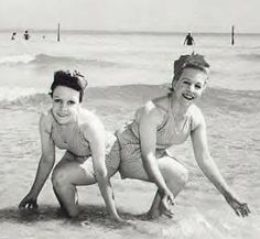 Original caption: Famous Siamese twins Daisy and Violet Hilton (of Freaks movie and sideshow fame) enjoy warm surf at Miami. (Feb. 25, 1945) Paul Colston Collection.