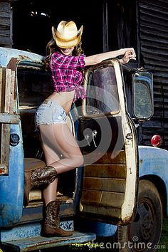 Sexy cowgirl poses with old truck by Macleoddesigns, via Dreamstime