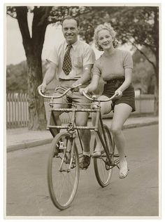 Man and woman on a Malvern Star abreast tandem bicycle, c. 1930s, by Sam Hood