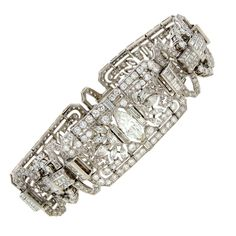 Stunning Art Deco bracelet with elaborate design, strong geometrical pattern and various diamond shapes. Created in the 1920's - 30's. Made of platinum and set with round, marquise, baguette, half-moon, pear-shape and emerald cut diamonds.
