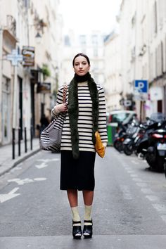 <3 her outfit. The light makeup with the darker green shade scarf around her neck. The stripes top with simple black skirt. Polka dot socks & black platform shoes. Over size bag & yellow/orange leather clutch/bag.