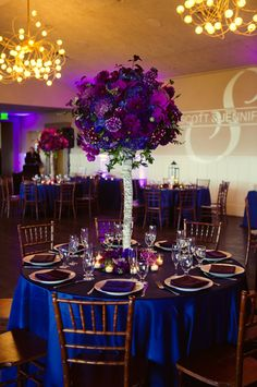 Purple and Blue Wedding Color Theme. Blue linens with centerpieces of blue and purple flowers. Dark brown chiavari chairs.