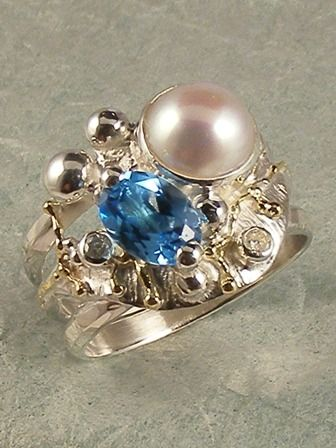 Piro band ring in sterling silver and 18 karat gold with facet cut blue topaz…