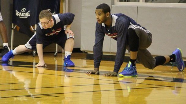 Referência Análoga (Nível de Relevância: 2) Kevin Grow stretching during practice with his new teammate. http://gma.yahoo.com/blogs/abc-blogs/down-syndrome-teen-free-throws-way-nba-contract-200953191--abc-news-topstories.html