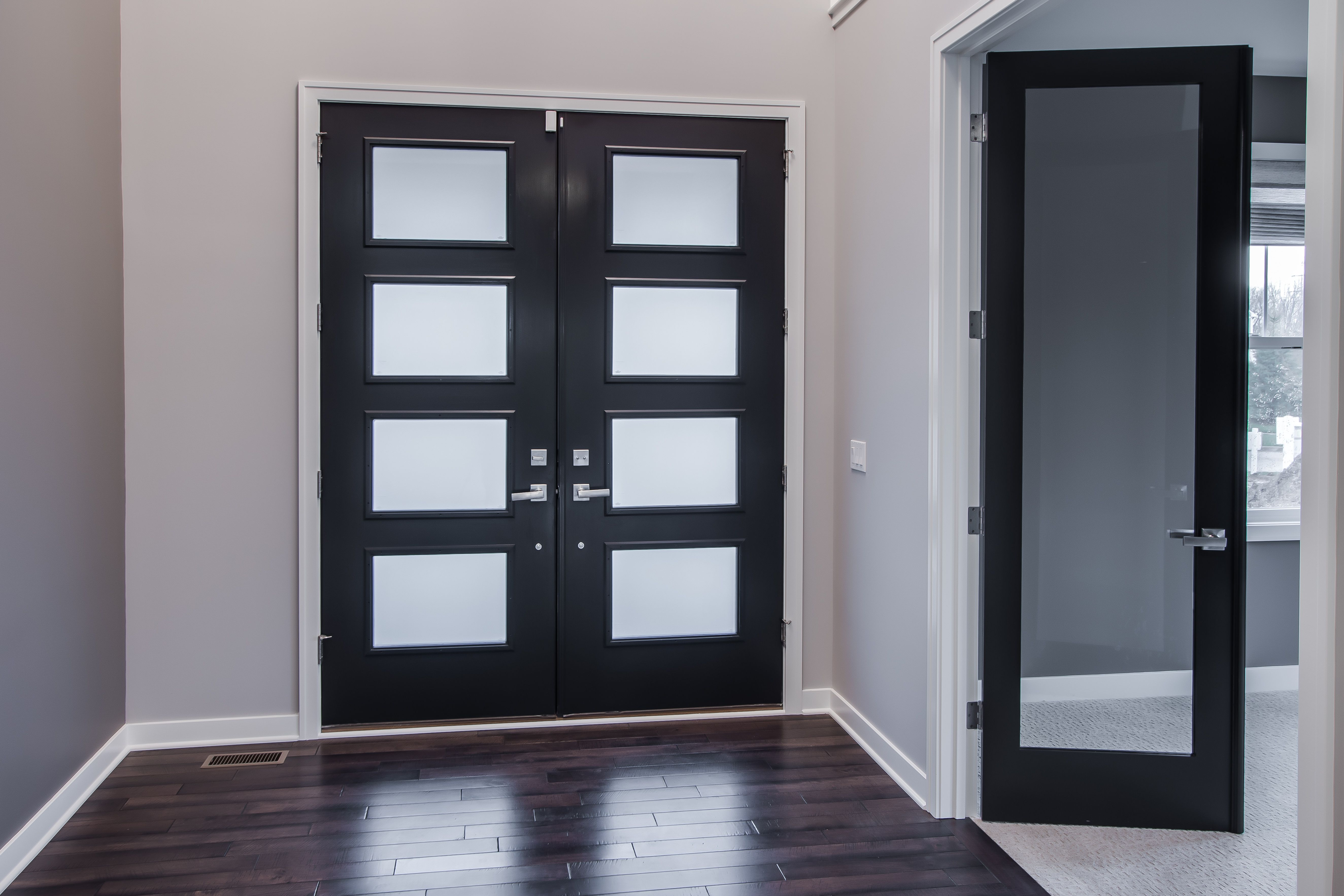 Foyer/Entry: Pecan Hardwood Floors, Black French Door Frames With  Translucent Window Panels