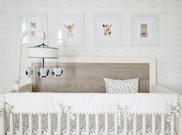 Dalmation spot bedding in this crib adds warmth to the light-washed wood headboard, while a gallery of framed animal prints inject personality.