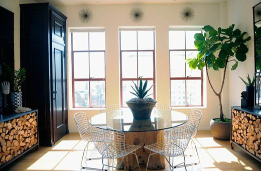 split wood. glass table top. white wire chairs. tall windows. light flooring.