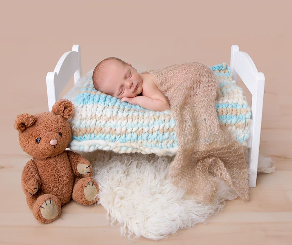 Baby blue and tan knitted prop blanket used as a layer here by made from love