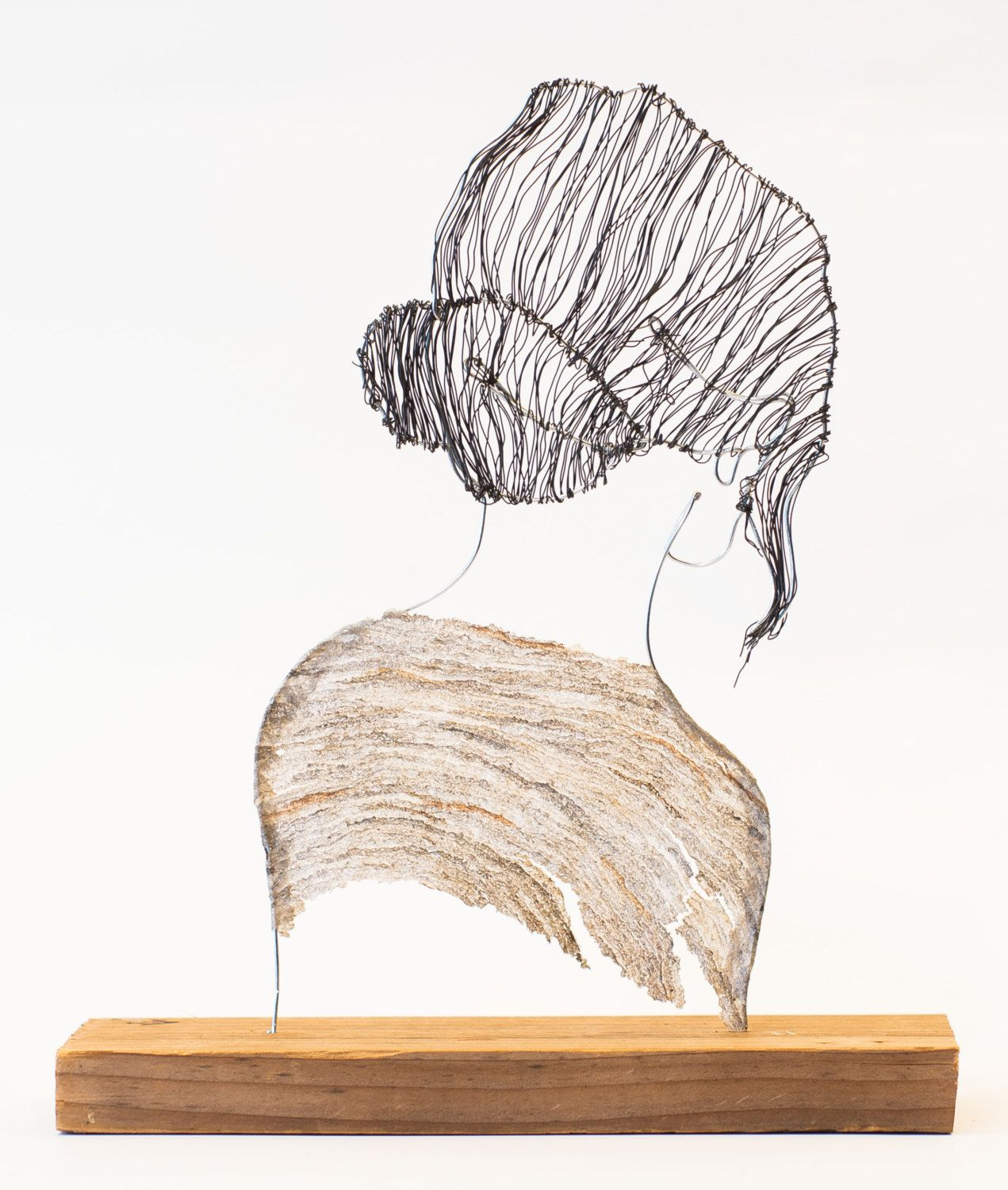 Wire sculpture of woman with hair in bun and paper wasp sweater