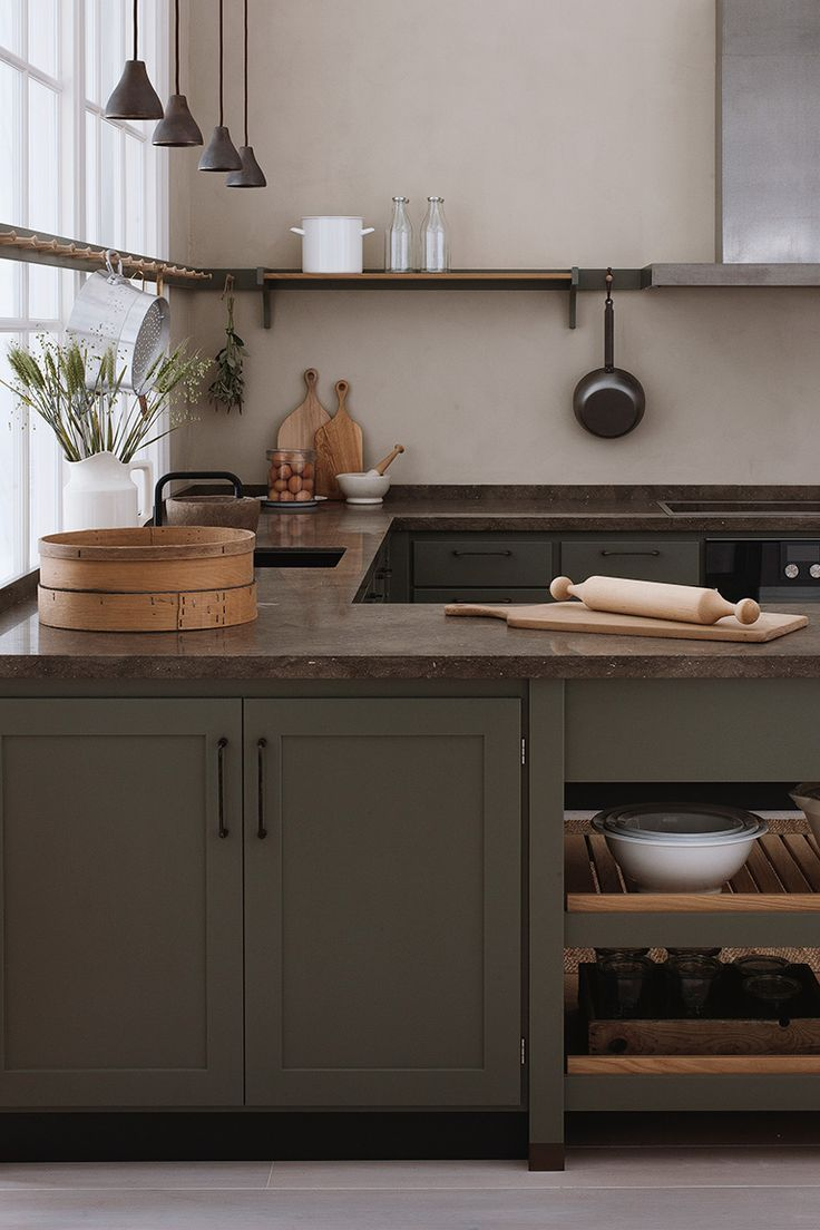 Photo of gorgeous kitchen with olive green cabinets, deep earth-colored marble counters, …