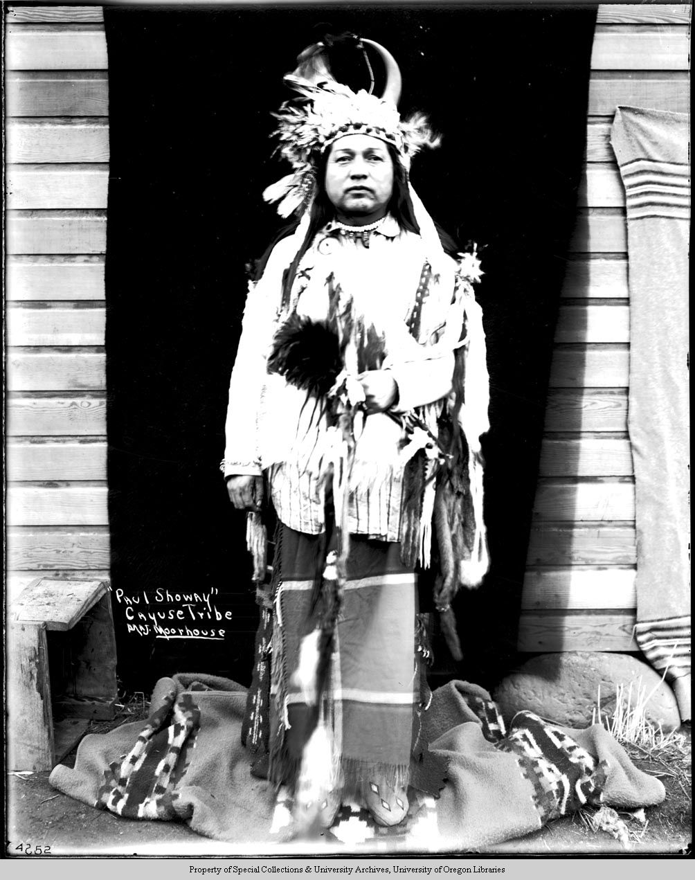 Paul Showay Cayuse  A Native American man standing outside against a black fabric backdrop hung from the side of a building. He is wearing a horned and feathered headdress, a buckskin shirt, geometrically-beaded moccasins, a necklace, and a blanket wrapped around his legs. He is holding an unidentified object in his left hand with hair or fur on the end of it.  Photo by Major Lee Moorhouse