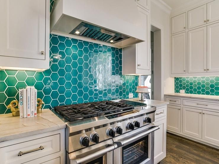 A White Vent Hood Is Mounted Against Teal Hive Backsplash Tiles Between Stacked White Shaker Cabinets Trendy Kitchen Backsplash Teal Kitchen Teal Kitchen Walls