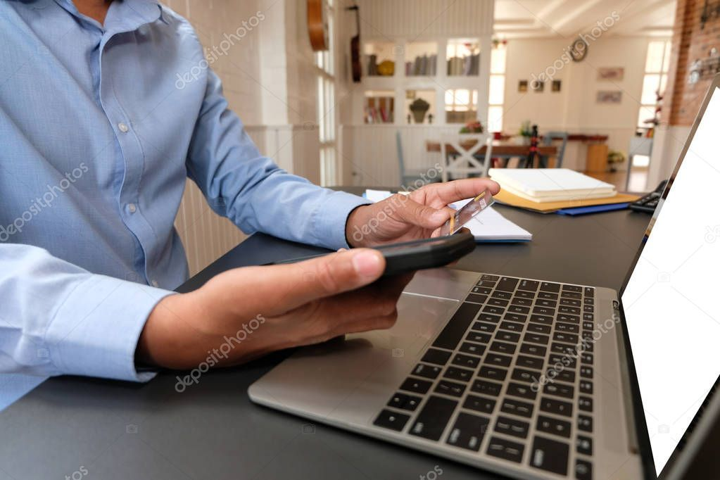 Man holding credit card using smart phone for online