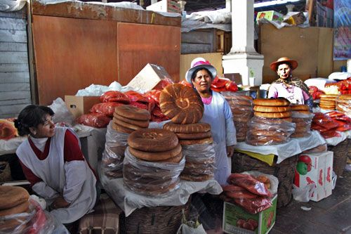 Quechua women at San Pedro Market in Cusco stand aside stacks of bread rounds.  Photo by Barbara Weibel.