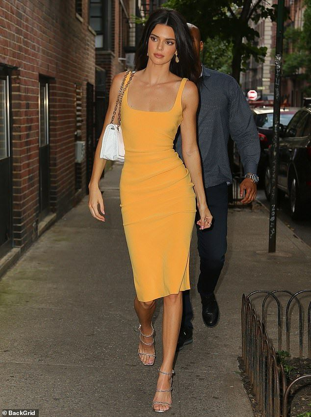 Kendall Jenner wears a tight yellow dress for a ph