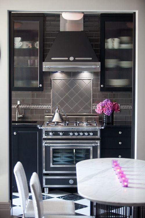 The Stove In This Kitchen Features Chrome Detailing That Draws In The Eye,  And Also Helps To Balance Out The Black Counters Around It. A Grey Tile ...