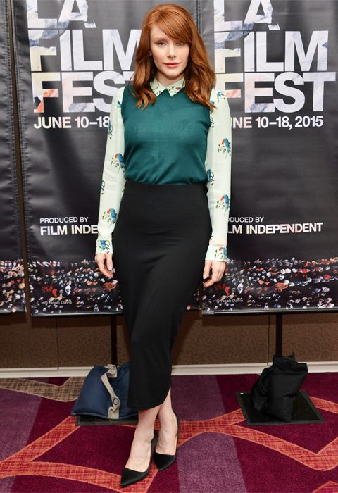 Bryce Dallas Howard in an emerald green sweater vest over a long-sleeve floral-print and demure midi-length pencil.