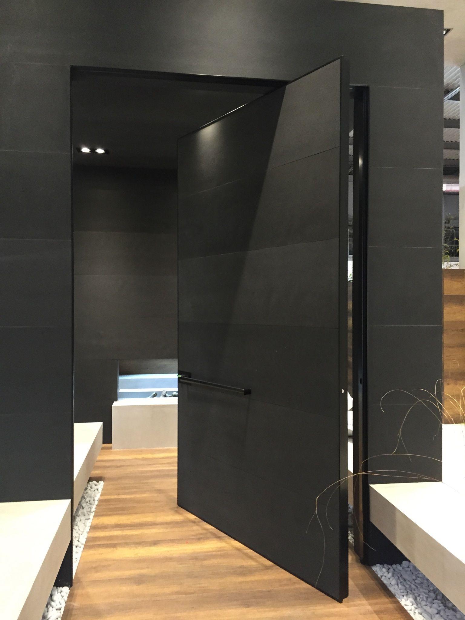Espectacular puerta Synua pivotante de grandes dimensiones 1800 x 2800 alto, en acabado cemento negro y guarniciones en aluminio Negro.