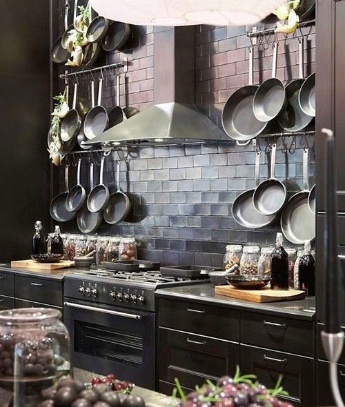 black appliances - love that the backsplash seems to reflect the sunlight. the hood is also super sexy. and seriously, how amazing are those pan racks? WANT!