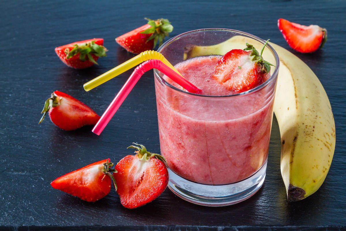 Banana strawberry smoothie ingredients dark stone background
