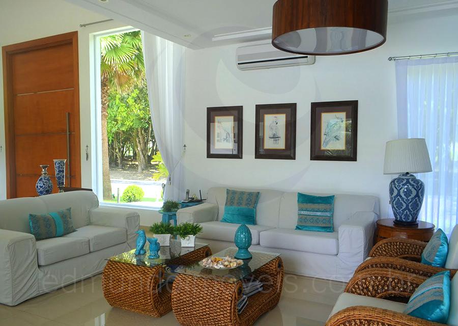 Um conjunto de sofás e poltronas em fibra natural decoram o estar, que conta ainda com o turquesa vibrante das águas paradisíacas da Praia do Pernambuco em almofadas e objetos de decoração.