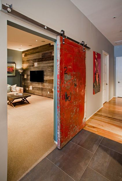 Salvaged fire door found at Olde Good Things in Scranton, Pennsylvania, hung in between the large, open area and a separate cozy den. track from Barn Door Hardware.