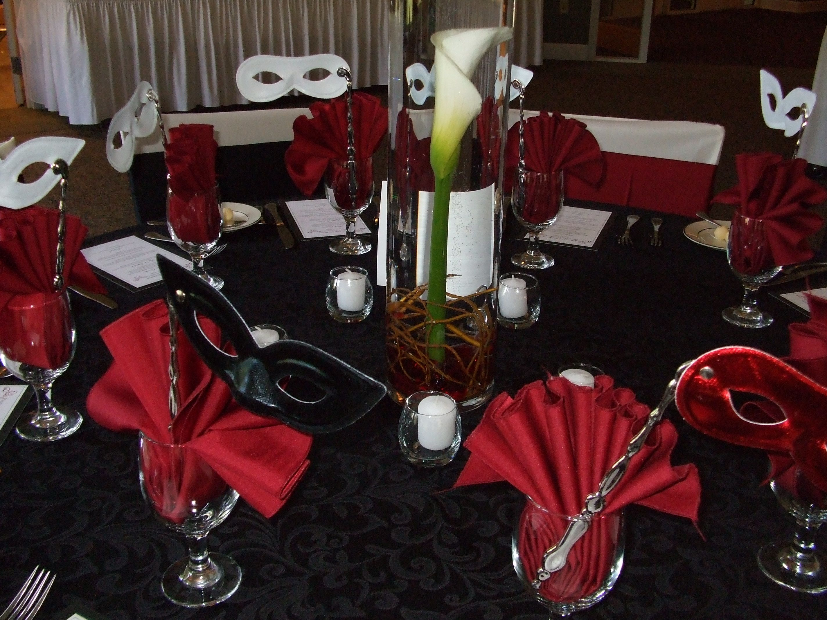 A Calla Lily stands out as the centerpiece of the table at this red and black reception