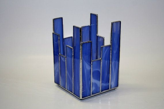 This medium blue colored stained glass candle holder measures 4 x 4 square and is 6 1/4 high at the tallest point. I made this using a medium blue with white streaks stained glass. This candle holder features a mirrored glass bottom to reflect the light of the candle. This candle holder has rubber feet on the bottom to protect your furniture. It comes with a tealight candle so you can begin to enjoy it immediately. All items in my shop are handmade by me in my home studio.