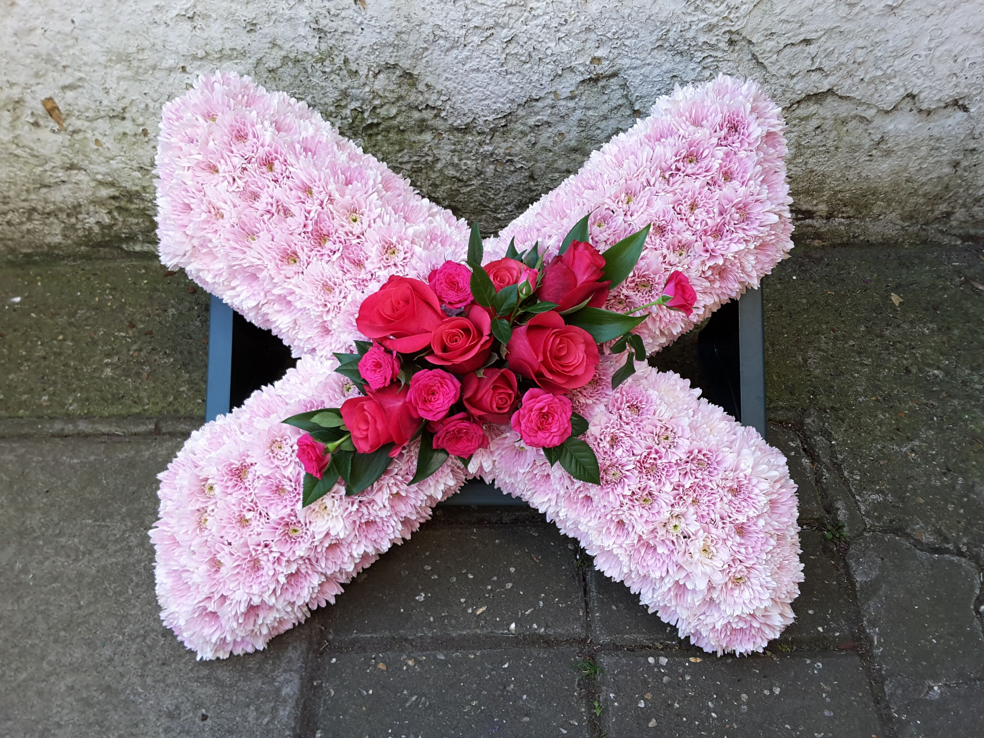 Pink based 'X' funeral tribute with a darker pink floral