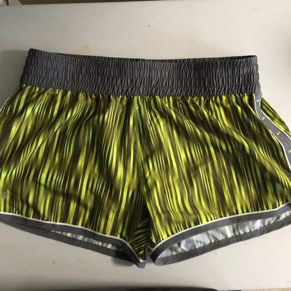Used under armour grey and neon green shorts Used large grey and neon green running shorts by under armour. There is a drawstring around the waist. The shorts are lined as pictured. Under Armour Shorts