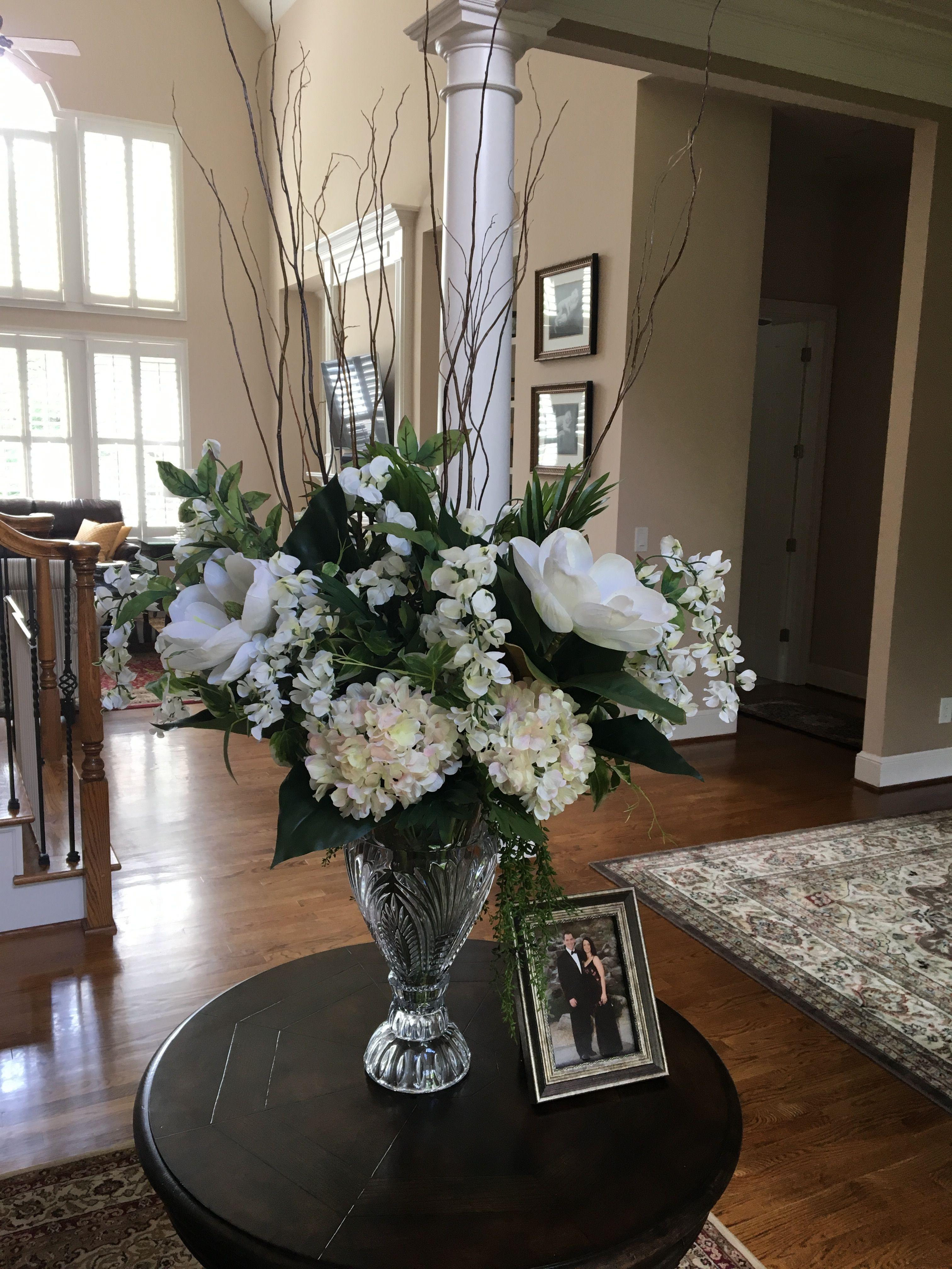 Foyer Silk Flower Arrangement In A Tall Crystal Vase Hydrangeas And Magnolias Framed Pi Crystal Vase Decor Flower Vases Decoration Flower Vase Arrangements