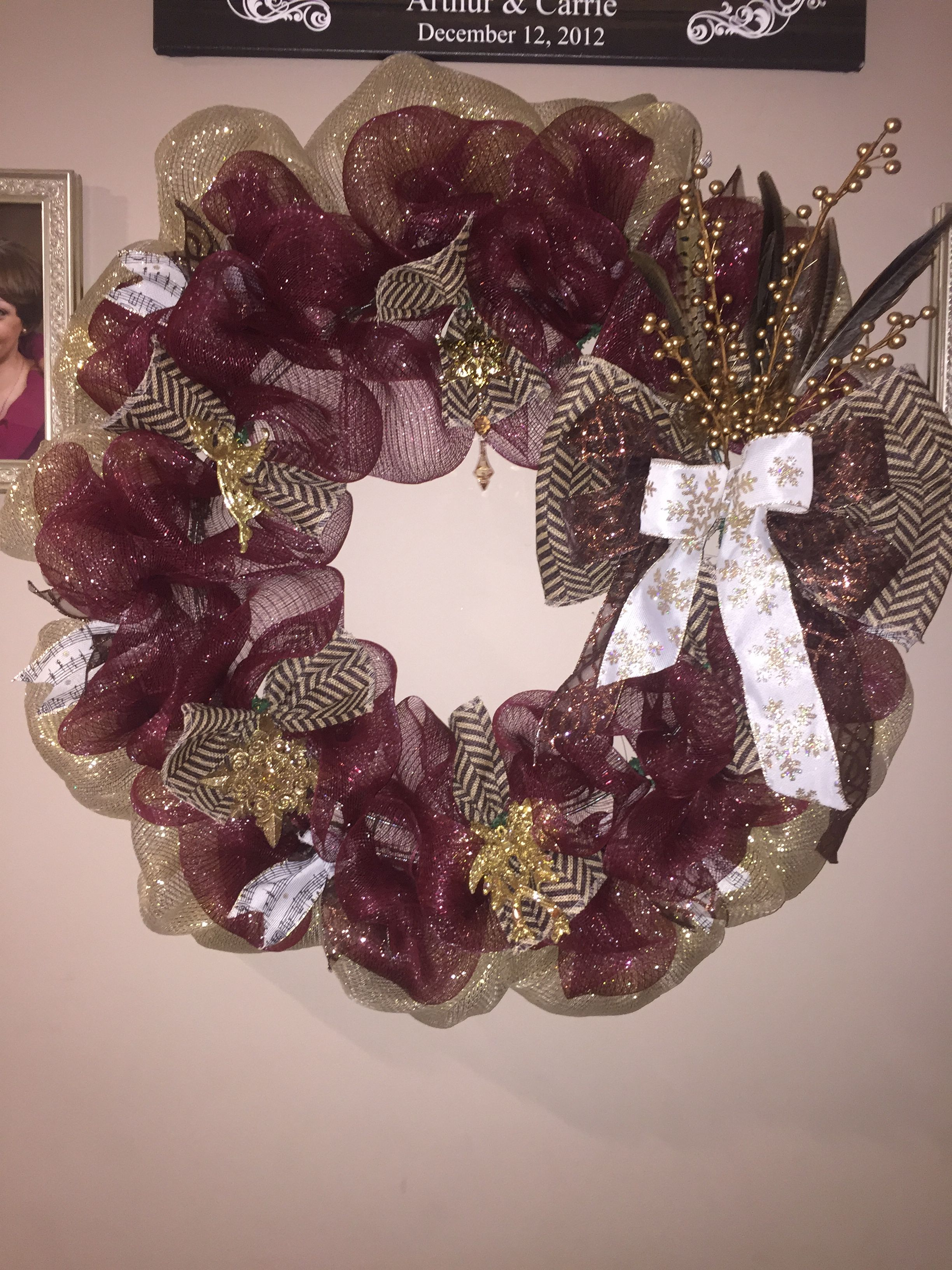 Burgundy and gold wreath with angels and star ornaments and feathers made by me.