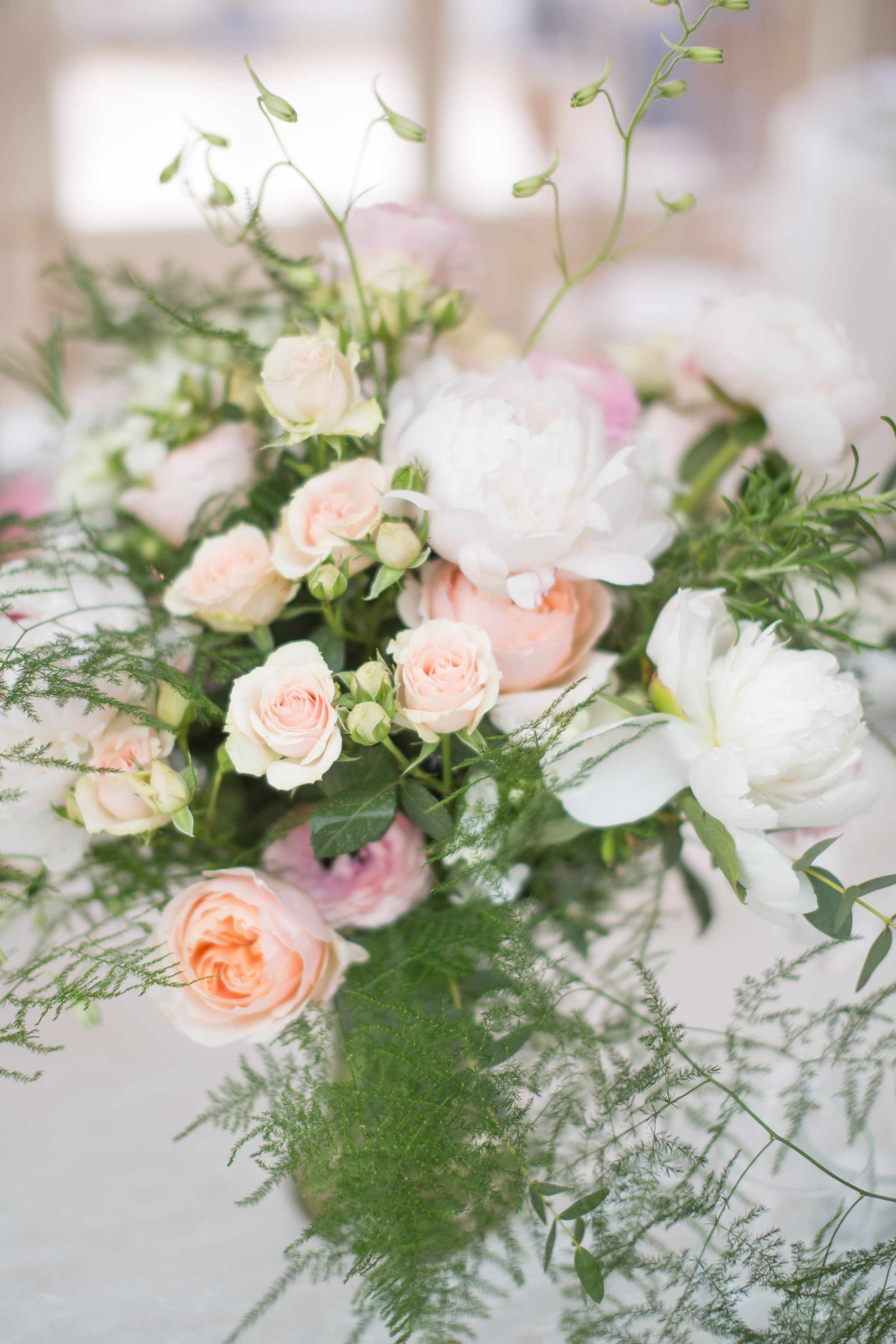 The Table centre pieces had a selection of flowers such as Peonie roses, small pink spray roses, sweet Pea, freesia and ranunculus flowers. Lamber de Bie, florist also used a selection of soft and romantic foliages such as eucalypthus and fern in these wedding flowers.