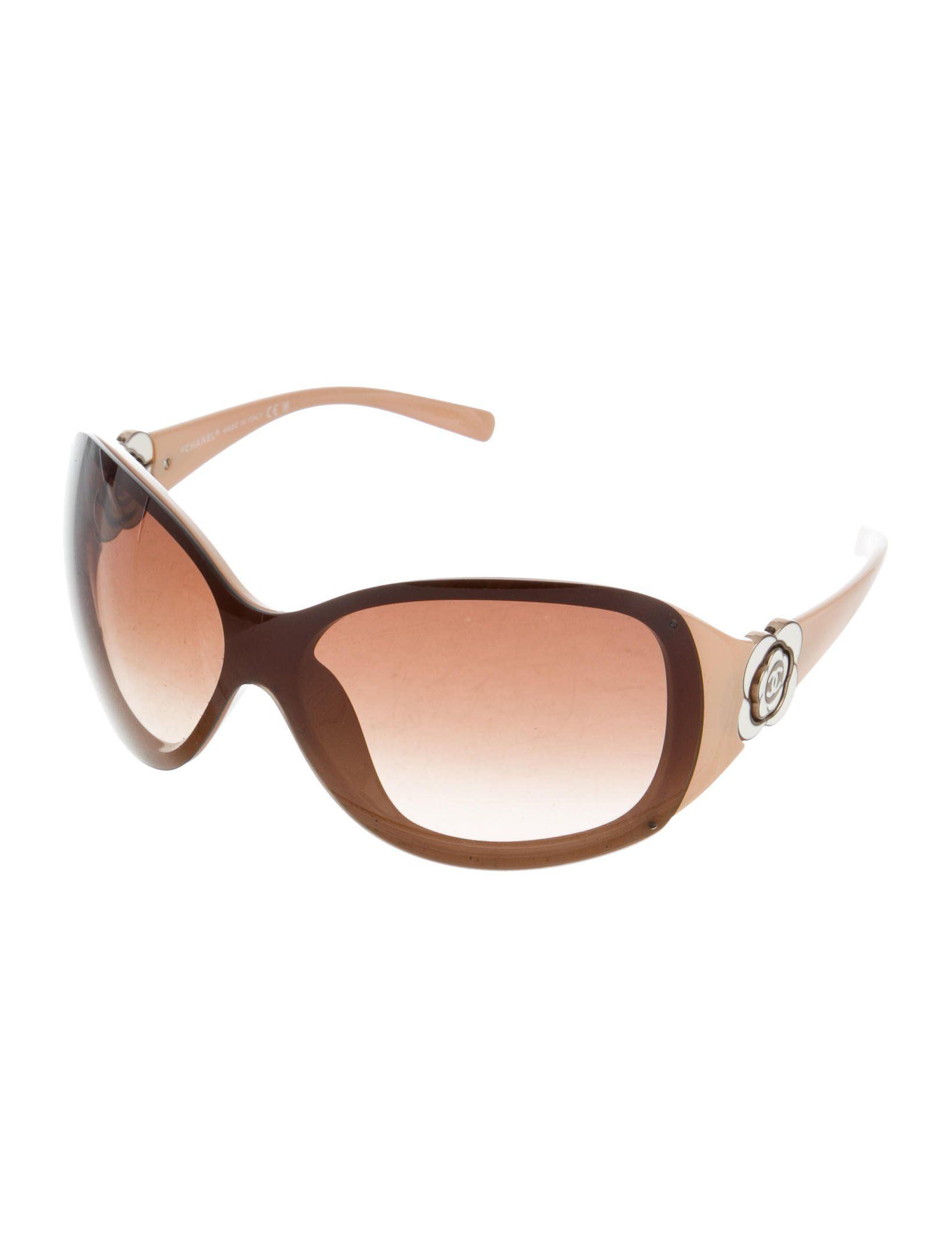 3252ba0f9d848 Brown and tan rimless Chanel shield sunglasses with camellia accents at  sides and gradient lenses. Includes case.