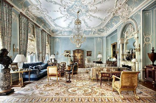 This ridiculously opulent Fifth Avenue Mansion has high ceilings, patterned drapes, tufted furniture, an ornate fireplace with mirror above and detailing trim and moldings.
