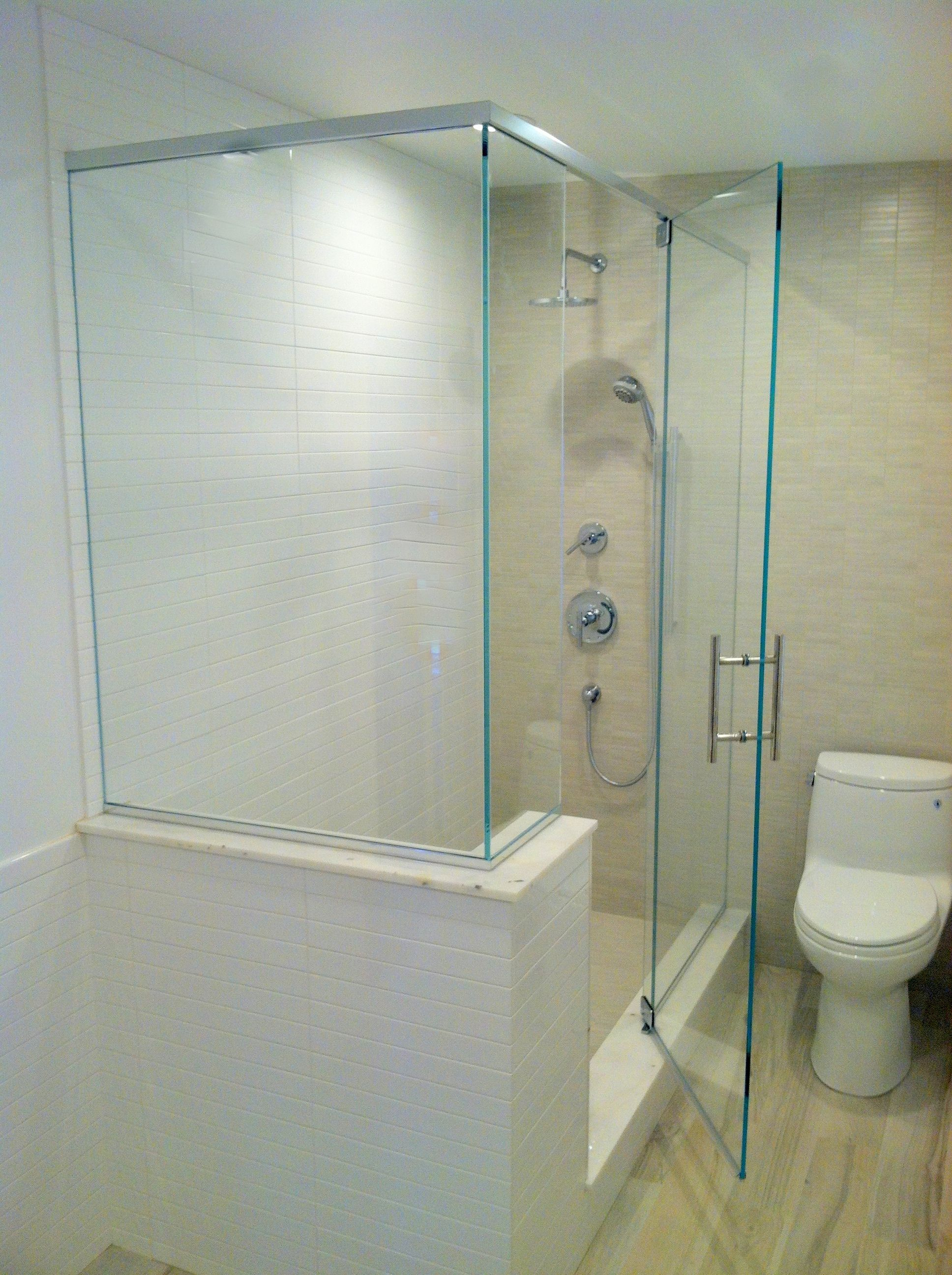 This frameless bath enclosure surrounds a shower with a bench seat ...