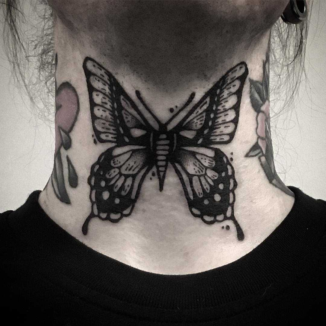 A black butterfly tattoo on a neck by Pulled Poltergeist