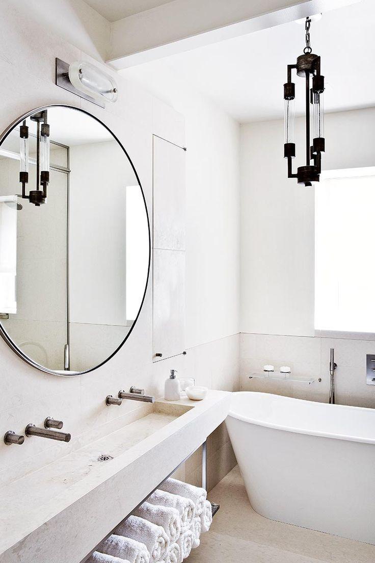 white bathroom, oversized circle mirror, lighing fixture, open ...