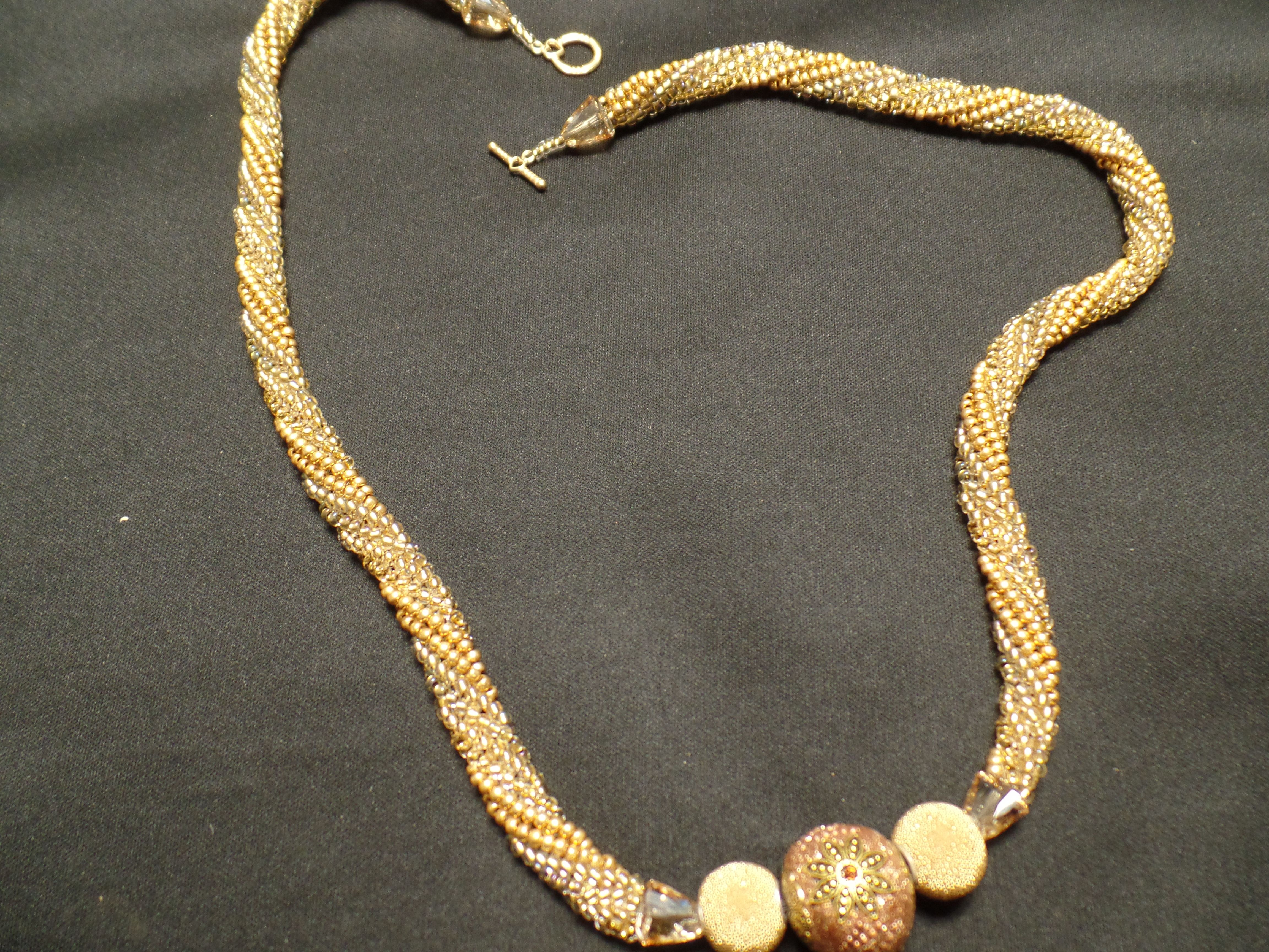 """Festive Holiday necklace made with three shades of gold beads, each finished with Swarovski crystal bead caps.  The fun center beads are from the Jesse James Bead Co. The necklace is 30"""" and ends with a toggle clasp.  $90.00 at www.mareekelley.etsy.com"""