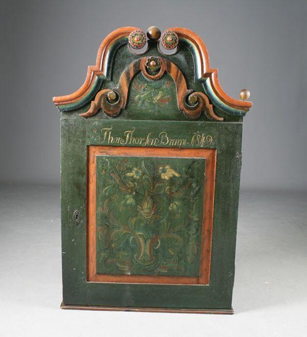 Rosemalt hengeskap med grønn bunnfarge, eiernavn Thor Thorsen Brenne 1849, Nedre Telemark. Pent malt innredning. H: 103 cm. B: 68 cm. Mangler kule. Prisantydning: ( 10000 - 12000) Solgt for: 11000