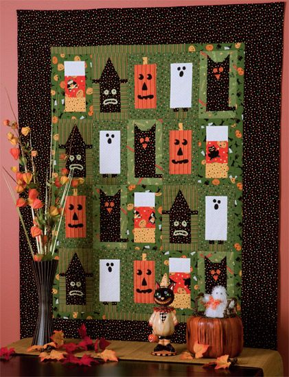 """Halloween quilt sporting pumpkins, ghosts and black cats. In """"Comfort and Joy."""""""