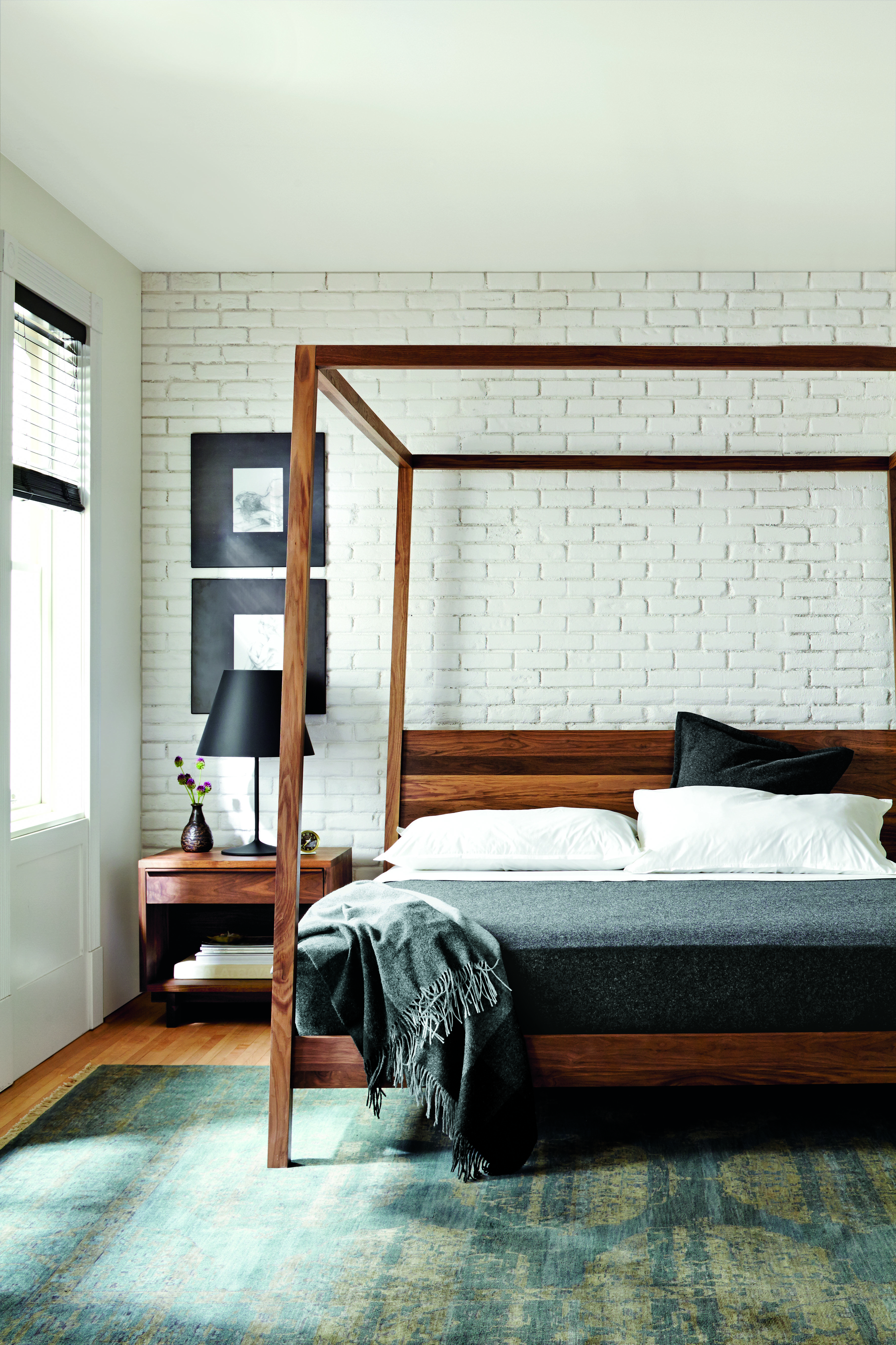 whitewashed brick complements a minimal wooden bed frame in this sleeksimple space. whitewashed brick complements a minimal wooden bed frame in this