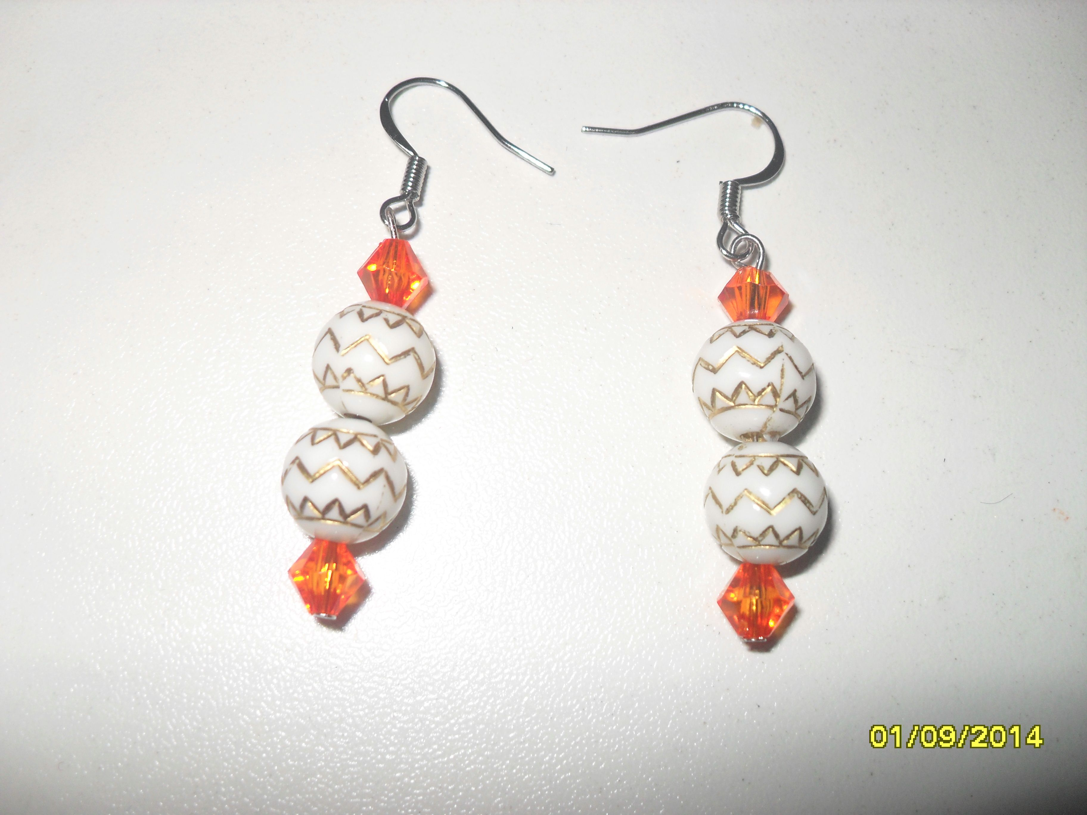 Small dangle earrings made with white round beads with gold design and orange diamond shaped beads.