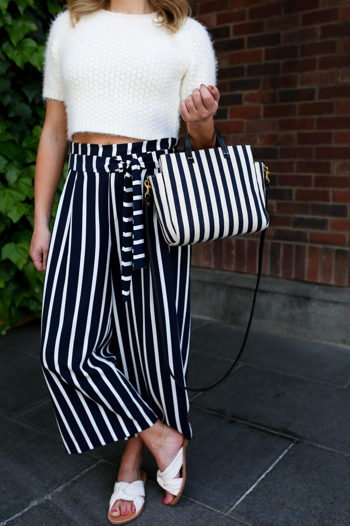 1714dd036dba5 Fashion and travel blogger Jessica Sturdy wearing a crop top short-sleeved  sweater with striped wide-leg pants and a Clare V mini stripe tote and  slide ...