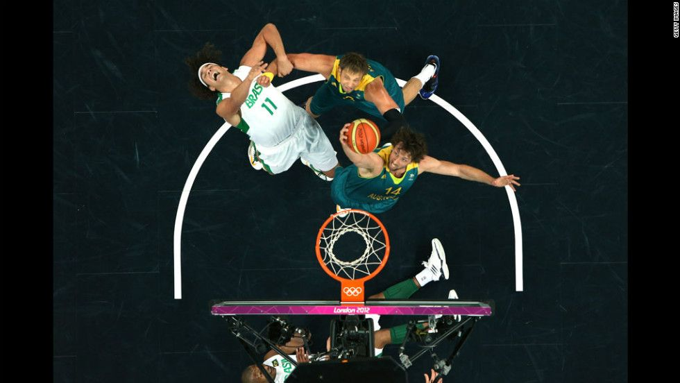 Brazil's Anderson Varejao, No. 11 in white, gets fouled by Australia's David Andersen, No. 13, as Anderson teammate Matt Nielsen, No. 14, right, goes for the rebound during the Brazil-Australia men's basketball game. http://www.PaulFDavis.com (info@PaulFDavis.com)