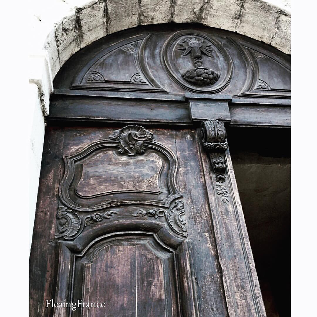 The pediment and door detail on a church with areas dating to the 1500's. #fleaingfrance #france