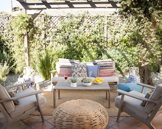 An Outdoor Patio With Washed Out Teak Wood Furniture And A Trellis Greenery Growing