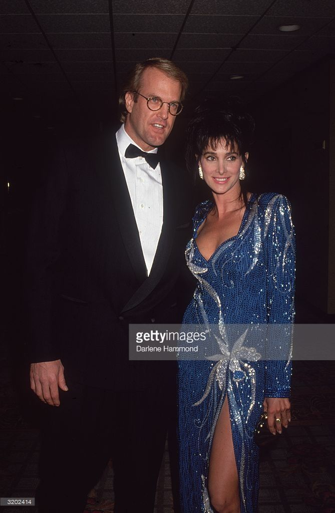 1995: American television personality and musician John Tesh, and his wife, American actor Connie Sellecca, attend a formal event. Sellecca is wearing a blue sequined gown with a slit up the leg and silver applique. Tesh is dressed in a tuxedo.