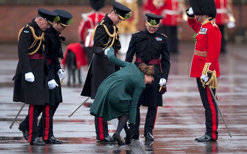 Prince William supports his wife, the Duchess of Cambridge, as she pulls her heel from a grate during a visit on St Patrick's Day to Mons Barracks in Aldershot